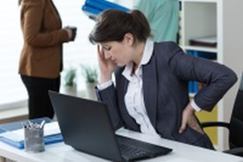 business woman showing pain at desk